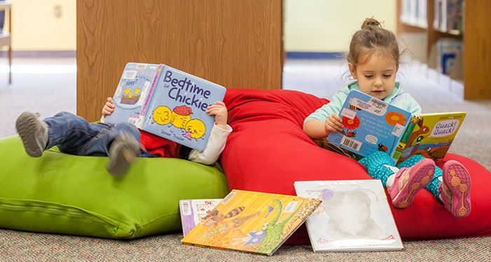 Two children reading books on beanbags